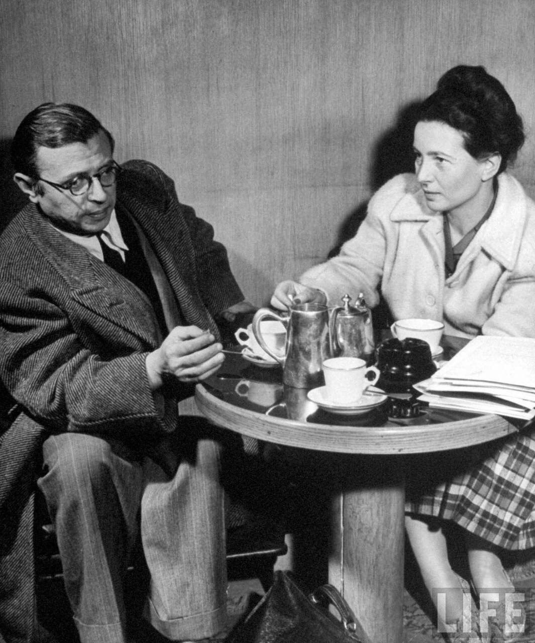 Jean-Paul Sartre and Simone de Beauvoir sitting at a cafe