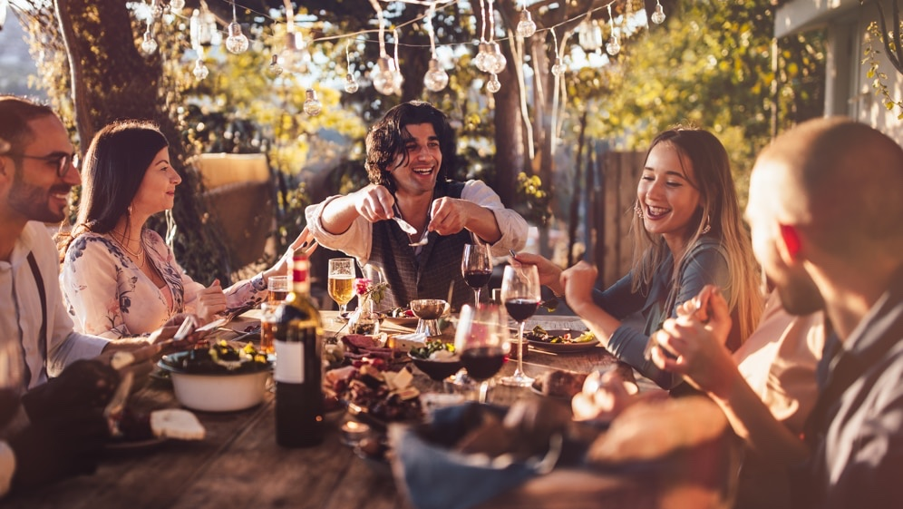 People eating and drinking wine